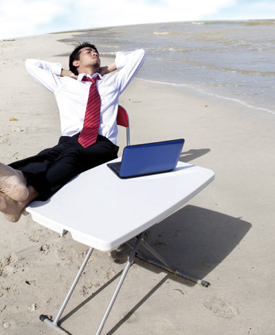 Man relaxing with a laptop on the beach