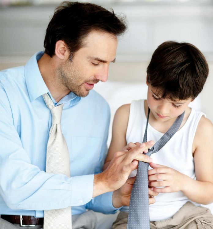 Father teaching his son to in tying a tie