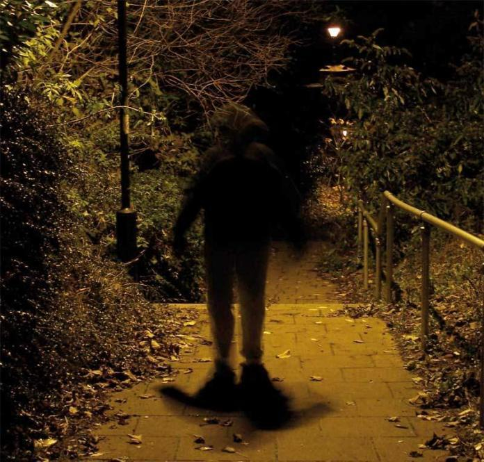 Man walking in dark light