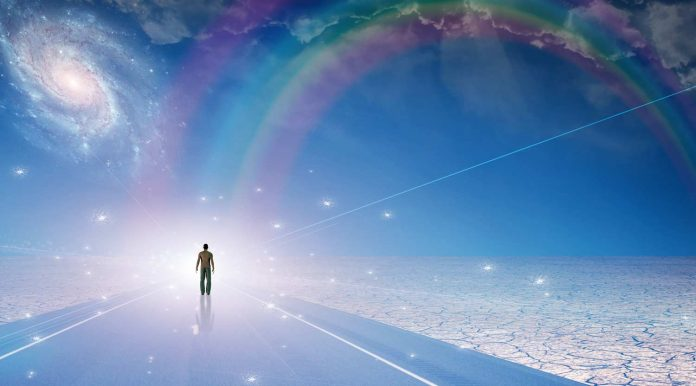 Man walking on an endless road with rainbow on the horizon
