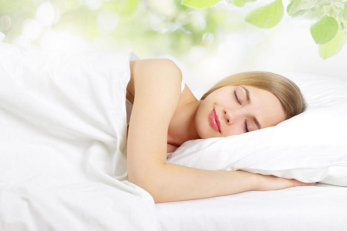 sleeping girl on the bed with leaves in the background