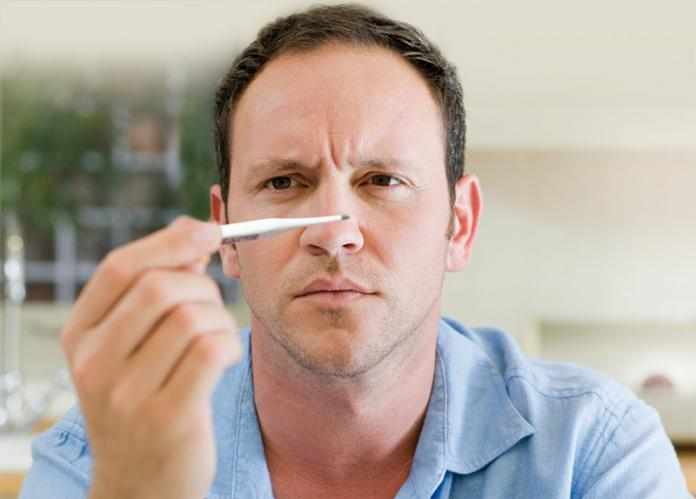 Man holding a thermometer