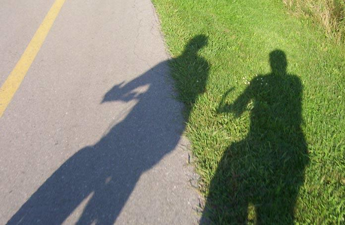 shadow of man and woman riding a bicycle