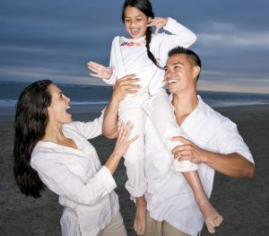Parents laughing with daughter on the beach