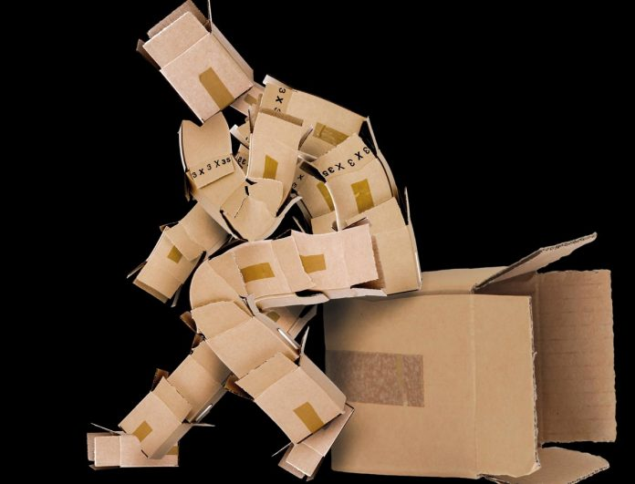 Man made of cardboard boxes thinking / clutter concept