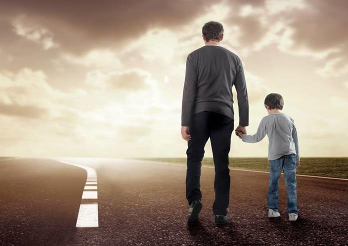 Father and son walking on an empty road