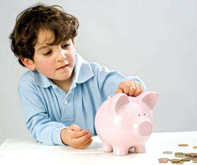 Boy putting coins in piggy bank