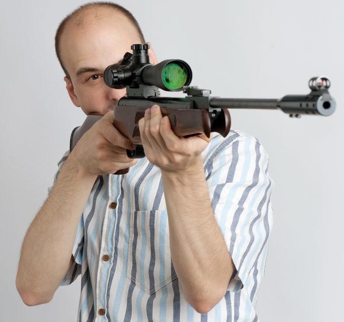 Man aiming to shoot with his rifle