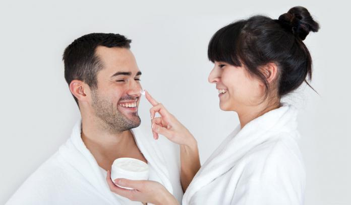 Woman applying face cream to man