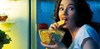 Woman eating from the refrigerator at night