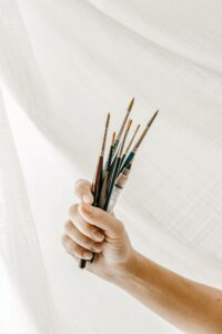 Paint brushes in an artist's hand