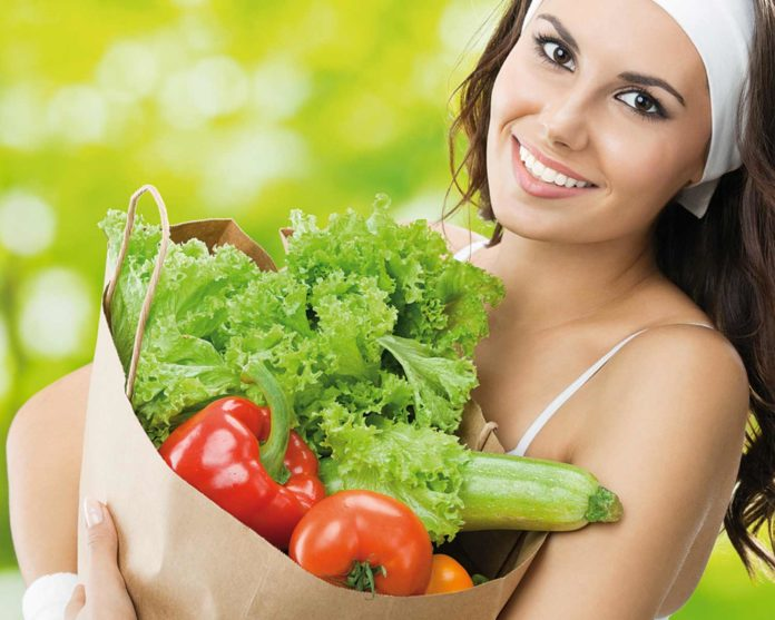 woman holding paper bag with fresh vegetables