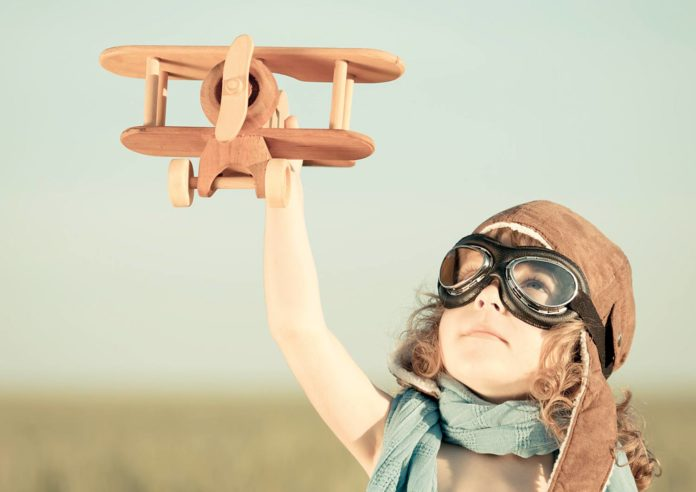 Girl child playing with a wooden made aeroplane
