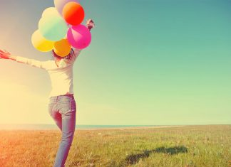 happy woman with baloons in an open field