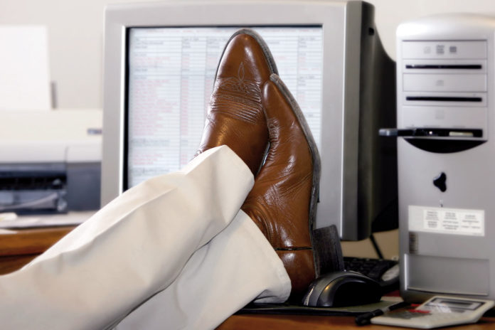 Man keeping his legs on the computer table during office hours