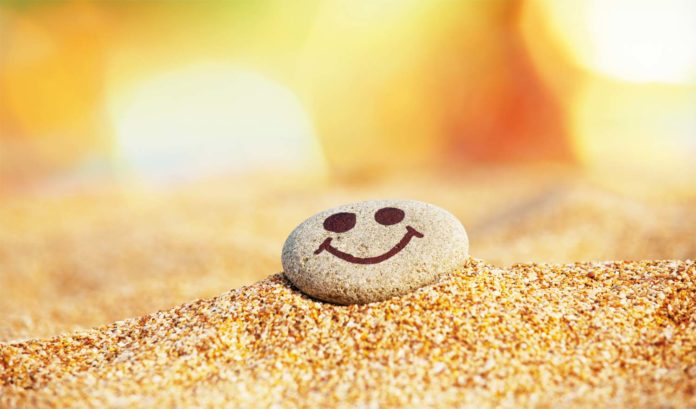 A smiley stone on the sand