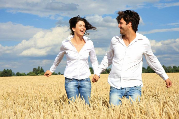 Man and woman holding hands enjoying in the paddy field