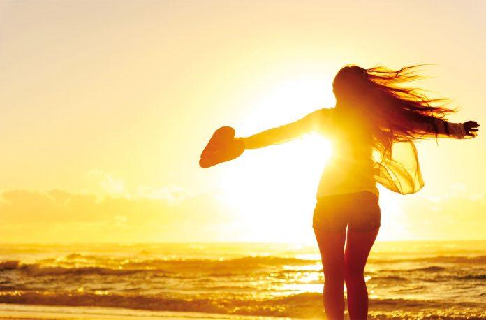 Women enjoying sunset by beach