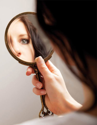 Woman looking at herself by holding a mirror