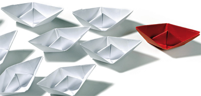 White paper boats with red one in lead
