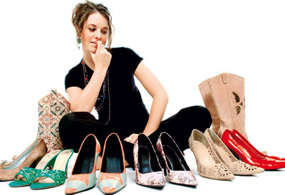 Woman sitting next to her collection of sandals
