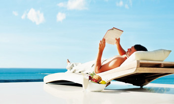 Man having leisure time reading a book on the beach