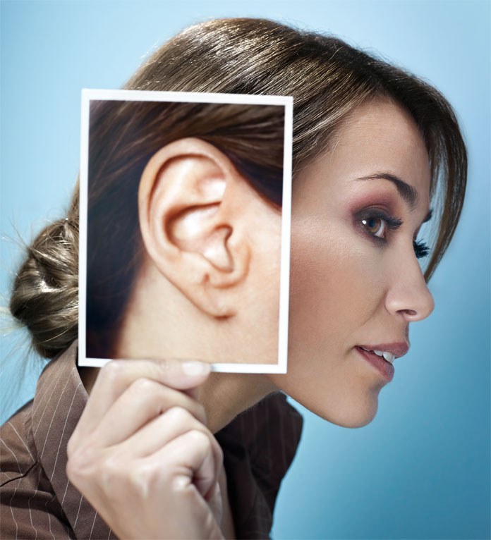 Woman holding a bigger picture of her ear