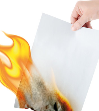 Man holding a paper which is on fire