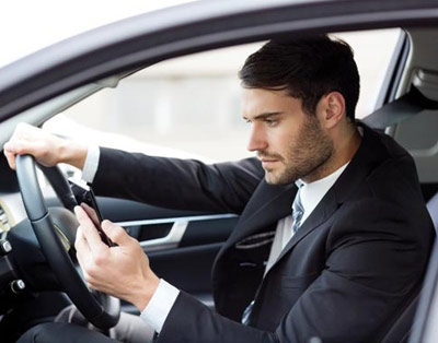 Man driving and texting message both simultaneously