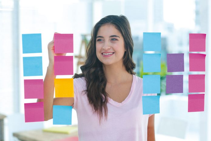 Woman preparing a list in post-it