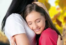 Teenager and woman hugging each other