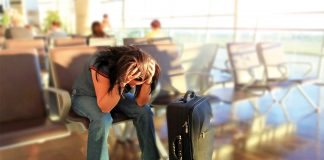Woman sitting at airport with hands on head; ruined holiday