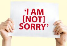 Holding a banner saying 'I am [Not] Sorry'