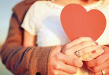 Couple holding each other with a heart shaped card — love is for the lucky few is a myth