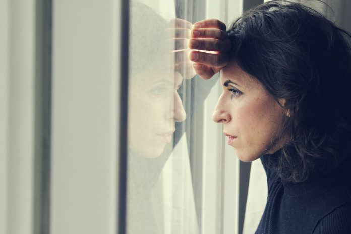 Sad woman gazing outside the window; coping with loss