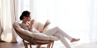 Woman reading book while drinking tea next to window with curtains