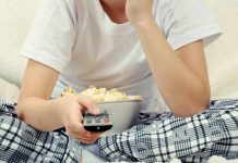 Boy with popcorn and TV remote in hand