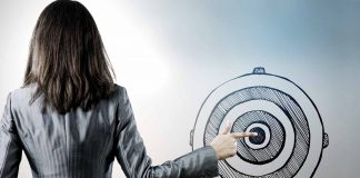 Woman in suit pointing finger on bullseye
