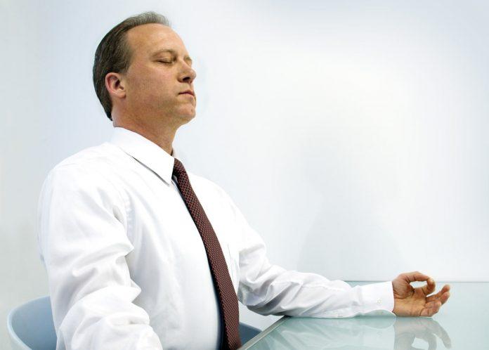 Man sitting in meditation at office