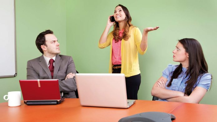 girl talking on mobile phone, colleagues annoyed