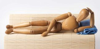 Wooden mannequin lying on the sofa
