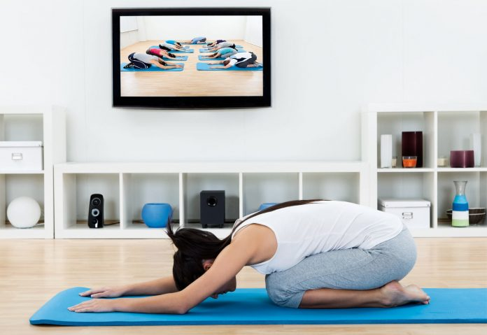 woman self learning yoga from instruction DVD