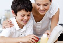 Woman teaching son to pack his tiffin; responsible children concept