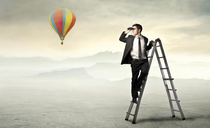 Man standing on a ladder and seeing far away with help of binocular
