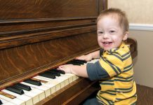 A differently abled child playing a piano