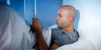 Man staring at smartphone screen lying in bed