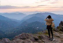 Girl admiring Bhimtal hills using binoculars