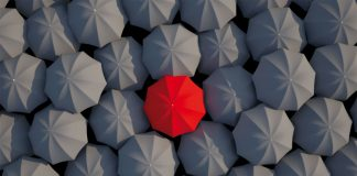 Red umbrella between black umbrellas