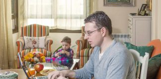 Man working from home on his laptop with his toddler in the background