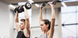 Man and woman with dumbbells in gym
